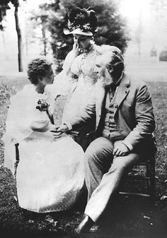 Alexander Graham Bell communicates by finger spelling with Helen Keller, who became both blind and deaf while still a young child. Miss Keller's teacher Annie Sullivan stands at centre.