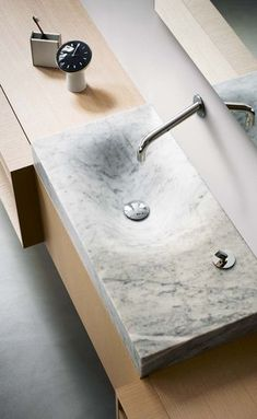 Marble sink, wooden table, toothbrush, clock