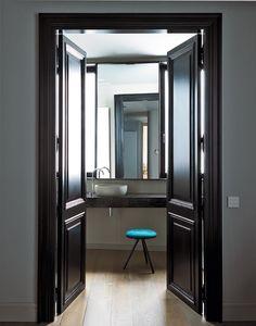 Porta laccata in nero lucido per il bagno con piano-lavabo in marmo Marquinia.