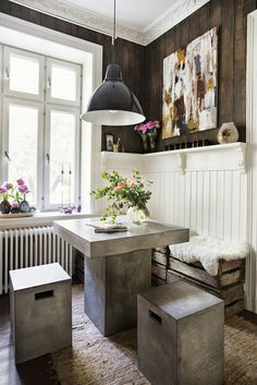Love the mixture of styles in this room. Ornate crown moulding, rustic barn wood walls, and modern concrete table and stools.