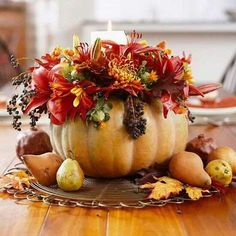Lilies, chrysanthemums, and pokeweed berries in a pumpkin vase