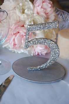 DIY Glitter table numbers (w/chunky glitter). I still don't get how these numbers stay standing with just hot glue gun