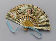A Victorian Bridesmaid's Fan, 1854-1887 | Fan with paper lead and gilded wooden sticks and guards. Made, 1854.  Given again in 1887. Usually fans of this size were made for children and were, therefore, roughly used and ultimately ruined.  The fan features a painted paper leaf with a scene of courtship and simple wooden sticks and guards. The reverse of the leaf is an elegant, but unadorned tan paper flecked with gold leaf.