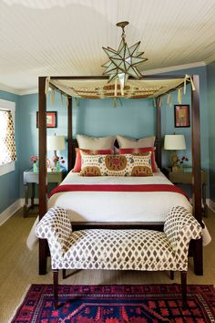 Turquoise walls add exotic flair. Wall-to-wall greige carpet was switched out for seagrass for a cottage look and layered with an antique area rug for added interest. The nondescript ceiling fan was traded for a Moroccan-inspired glass lantern that makes a bold statement. The four-poster bed tented with a custom canopy serves as the room's focal point.