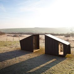 These two charred-timber cabins house a temporary artist's studio that will travel across the UK