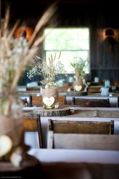 Rustic wedding reception table decor idea - baby's breath in large mason jars wrapped with burlap on top wood slices.