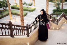 """Laden Sie das lizenzfreie Foto """"Muslim woman holding shopping bag and smart phone. Typing message."""" von dusanpetkovic1 zum günstigen Preis auf Fotolia.com herunter. Stöbern Sie in unserer Bilddatenbank und finden Sie schnell das perfekte Stockfoto für Ihr Marketing-Projekt!"""