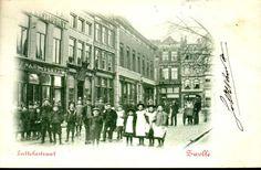 Gezicht vanuit het zuidoosten op het begin van de Luttekestraat en de Voorstraat. Uiterst links (Luttekestraat 10) is het cafe-restaurant van Frans Vulker gevestigd. Op de gevel van Voorstraat 8 maakt J. van Eelen reclame voor matten en schuiers. Op Voorstraat 4 is kruidenier J. Hollander gevestigd.