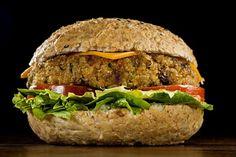 Hambúrguer veggie do Madero, com quinoa e aveia - 200 g de quinoa, 100 g de aveia em flocos, 10 g de salsinha, 10 g de cebolinha, 40 g de alho-poró, 25 g de shoyu, 1 pitada de pimenta do reino, 13 g de óleo de milho, 35 g de farinha de rosca, 240 ml de água, 35 g de farinha de trigo integral, sal, páprica doce, cúrcuma e pimenta a gosto, 50 g de cebola triturada, 2 g de alho triturado, 10 g de óleo de milho para refogado, 60 g de cenoura, 35 g de cebola, 2 g de alho.