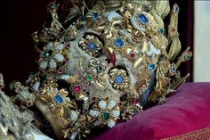 400-year-old remains are adorned with dozens of jewels, gems and a gold leaf crown. In the hollows of the eyes sit two gold brooches, set with a blue gem and pearls.