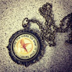 The Hunger Games necklace featuring the Katniss' Mockingjay pin and May The Odds Be Ever In Your Favor by TheSlingsAndArrows on Etsy, $16.00