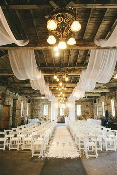 White fabric runners through ceiling beams add an elegant touch to a rustic building.