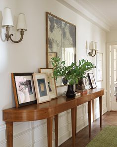Classic Meets Colorful  Propping framed pictures on the foyer console lets the family rotate its art collection easily.