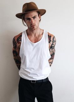 handsome male model wearing loose white top, hat, and black pants