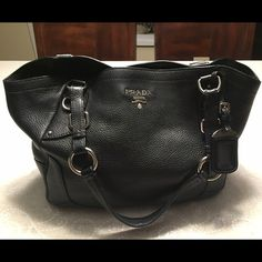 """Prada tote bag Pre-loved black pebble leather Prada tote bag. Silver hardware. Bought at Prada outlet store in 2010. Comes with dust bag, authenticity card. 17"""" width X 11"""" height, strap drops 9"""". Prada Bags Shoulder Bags"""