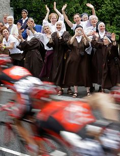 """[Real] """"Nuns applaud as the pack passes through Lourdes during the 10th stage of the Tour de France between Pau and Hautacam, southern France, Monday July 14, 2008. (AP Photo/Bas Czerwinski)"""" #letour #TdF #cycling"""