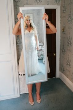 Maid of honor holding the mirror for the bride