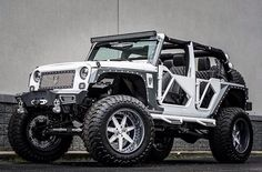 BLACK AND WHITE JEEP WITH UNIQUE DOORS. GREAT LIFT AND WHEELS!