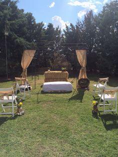 Altar con alpacas de paja, cortinas y lazos de silla con tela de arpillera. Detalles de tarros de cristal decorados a mano y flores para adornar