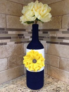 This lovely magnum size wine bottle (1.5L) is wrapped in navy blue and white yarn accented with a yellow burlap flower and button. Can be