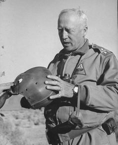 Gen. George S. Patton Jr. inspecting a tankers helmet while on training maneuvers in the desert in California. 1942 Photographer: John Florea