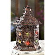 Pretty Mini Jeweled Candle Lantern - The glow of candlelight will make this Pretty Mini Jeweled Candle Lantern sparkle and shine like a jewel! This iron lanterns panels are adorned with colorful gems and the intricate cutouts will create beautiful ambiance with the help of a single candle.