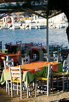 Outdoor Greek tavern dining space by the sea with white wood tables, chairs and colorful tablecloths.