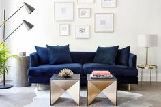 Beautifully designed contemporary living room features an art gallery mounted above a blue velvet sofa flanked by a round concrete side table and a round brass end table topped with a brass and glass lamp.
