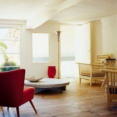 Un salon aux murs blancs et plafond lambrisé