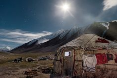 Blanket-draped yaks hunker down outside a young couple's yurt on the eve of a summer trading journey. Made of interlaced poles covered with felt, these portable homes are packed up and reassembled for seasonal migration. Wooden doors are imported to the treeless plateau from lower altitudes.