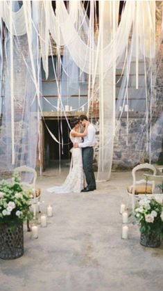 Dramatic wedding backdrop created with layers of sheer fabric and ribbon.