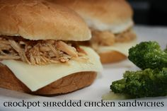 Crockpot Shredded Chicken Sandwiches  recipe from Going Jane      3-4 boneless skinless chicken breasts  1 packet onion soup mix (like Lipton)  1/4 cup zesty italian salad dressing  1/4 cup water  garlic salt to taste  hamburger rolls  swiss cheese (optional, but totally tasty)