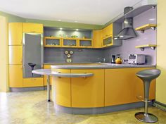 This unique kitchen design has curved yellow cabinets, a stainless steel hood, and a lavender gray countertop & backsplash
