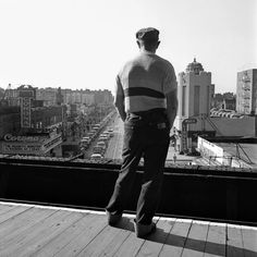 A man with a cap on a roof looking down at the street with the Corona Theater. March, 1953 New York, NY
