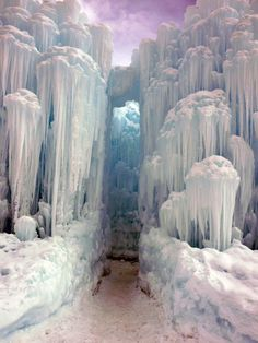 """Ice Castle in Midway, Utah, by Brent Christensen - photo from Been There, Done That blog;  """"Although the structures grow organically, formed by dripping water and freezing temperatures, their growth has to be pre-planned and guided. ... The structures have to be maintained ... which means Brent and his crew literally scale the structures with special climbing gear like arctic explorers."""""""