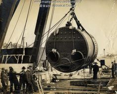 """Marine boiler built by the Portland Company, Portland, Maine ca. 1900.  """"Here we see a Scotch-type marine boiler being lifted by the Portland Company A-frame derrick and about to be lowered below through an opening in the deck of a vessel tied up at the company pier."""" Item # 8017 on Maine Memory Network"""