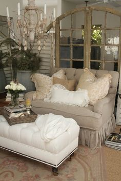 A shabby chic seating area with tufted beige sofa and a white tufted ottoman. Mirrors, plenty of throw pillows and a chandelier are the glamorous finishing touches.