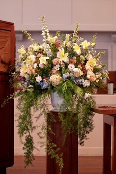 A simply beautiful overflowing spring arrangement bring the outside indoors for Jesse and James' ceremony. Any Tucker Photography.