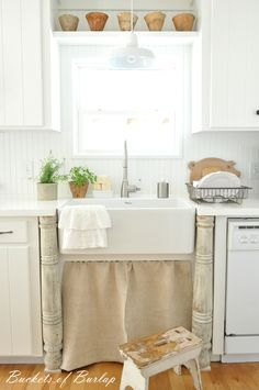 Farmhouse kitchen. Painted white countertops and grainsack sink skirt