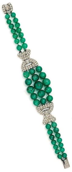 An Art Deco Emerald Bead and Diamond bracelet. The graduated three row emerald…