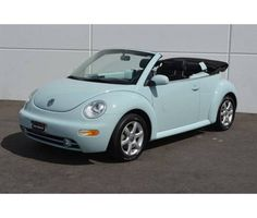 A bug convertible probably in a light blue or pearl white