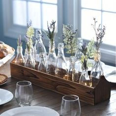 Decorating with glass continues to be a hot trend. With its sleek lines and vintage reclaimed look, this Rustic Boxed Bottle Tabletop Centerpiece will add a chic understated elegance that surpasses all others. Use the glass jars to showcase flowers, or leave them empty for a vintage vibe. Employ it as your dining room centerpiece, use on your foyer table, or put it in your kitchen, bedroom or bath as a stylish decor piece.