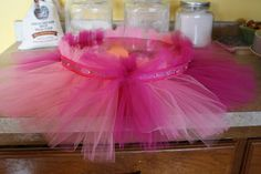a tutu cake stand using tulle, ribbon, scrapbook paper, and a styrofoam cake round.