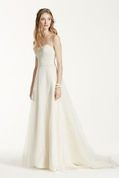 Ethereal elegance meets modern day fairy tale in this enchanting strapless tulle wedding dress!  Strapless A line gown features stunning beaded lace detail on bodice.  Soft tulle skirt adds movement and is absolutely breath-taking.  Sizes 0-14. Sweep train. Fully lined. Back zip. Imported polyester. Dry clean.  Ivory/Champagne available in stores and online. Solid Ivory and Solid White available for Special Order in stores.   Woman: Style 9WG3586. Sizes 16W-26W.   Extra Length: Sty...