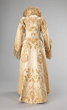 Dramatic Art Nouveau Silk Evening Coat | c.1902 | House of Worth, Paris | Designer: Jean-Philippe Worth | French| Silk, Lace | Length at CB: 63 in.(160 cm)| Gift of Mrs. C. Oliver Iselin, 1961| Accession #2009.300.308| This dramatic coat is very indicative of the Art Nouveau style which was popular at the turn of the century. The sinuous curves of the textile & the symmetrical seaming make this exemplary of the House of Worth's design aesthetic.| (Back)