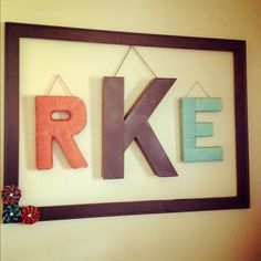 Cardboard letters wrapped in yarn. Centered in an empty frame with rosettes.