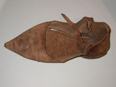 Pointed shoe fastened by a strap and buckle. This shoe has quite a modest point - other shoes of this 'poulaine' type had very long points which had to be stuffed with moss to keep their shape. Medieval shoes were made by 'cordwainers' (the word comes from 'cordwain', or 'cordovan', the name for the leather made in Córdoba, Spain). TL74[275]<2005> and TL74[275]<2011> are part of the same shoe. Museum of London
