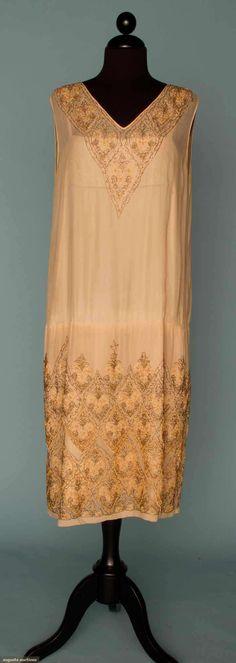 GOLD & SILVER BEADED DRESS, MID 1920s  Cream silk chiffon sheath, v-neck & double flounced hem, embellished w/ gold & brown beads, matching silk charmeuse & lace slip.