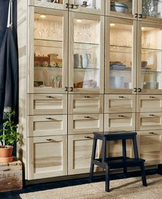 A large wall of kitchen storage with ash veneer drawers and glass-door cabinets.