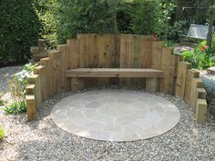 Raised timber sleepers to create a fire pit and seating area, complete with Indian Sandstone circle kit and gravel garden surround.